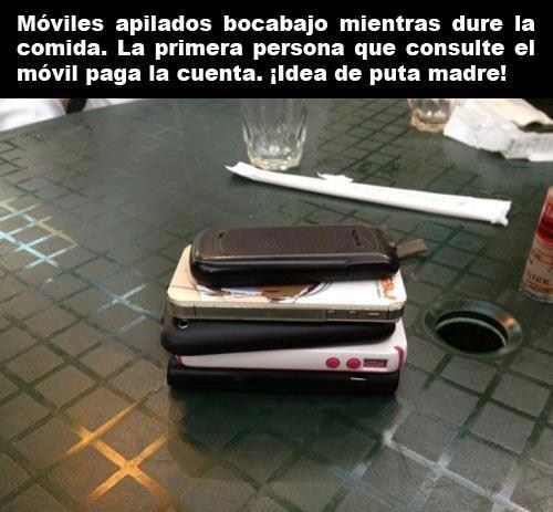 moviles apilados boca abajo durante la comida el primero que consulte paga la cuenta